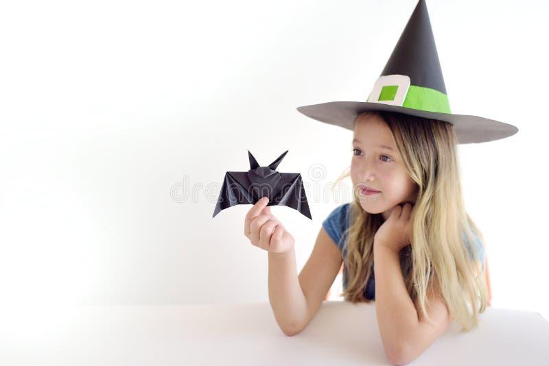 Девушка играет в добившийся успеха своими силами маске ведьмы на хеллоуин стоковое изображение rf