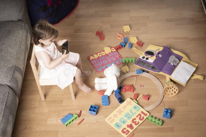 Девушка играет мобильный телефон Девушка закреплена к мобильному телефону Он не играет с игрушками Мобильный телефон плох для дет стоковые изображения rf