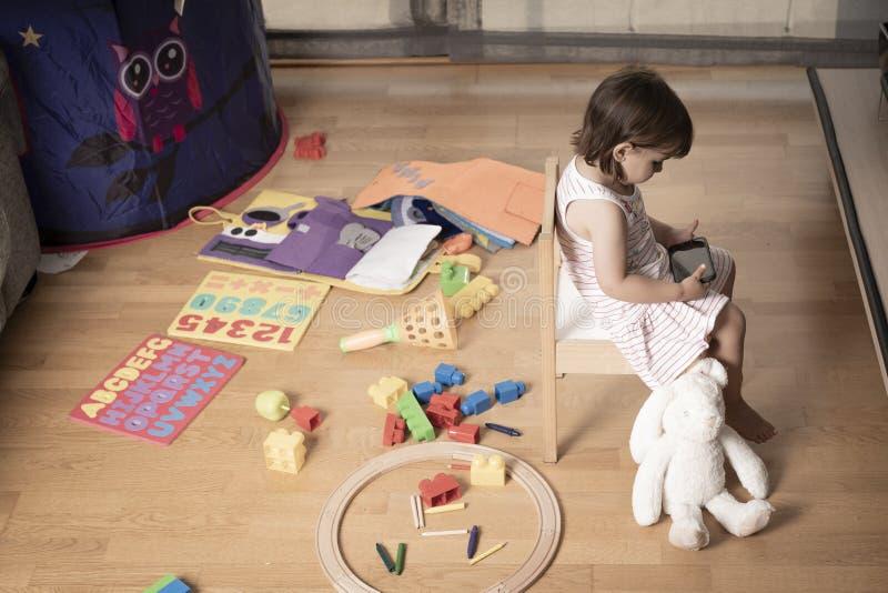 Девушка играет мобильный телефон Девушка закреплена к мобильному телефону Он не играет с игрушками Мобильный телефон плох для дет стоковое изображение