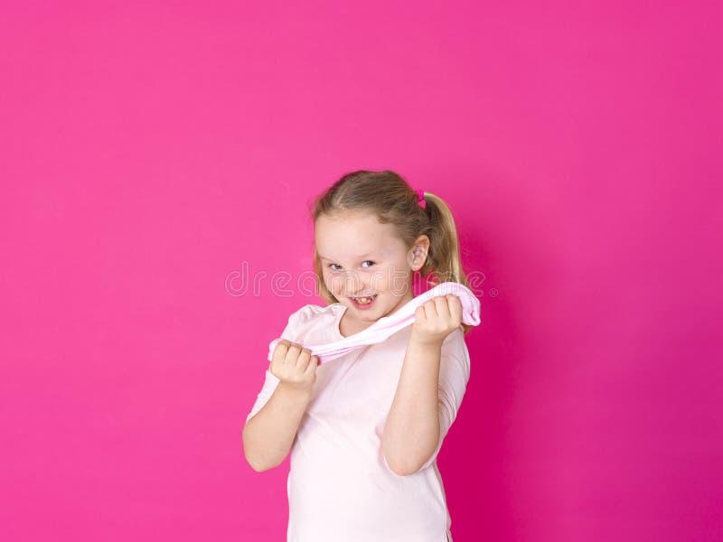 Девушка играет с желтым шламом перед розовой предпосылкой стоковое изображение