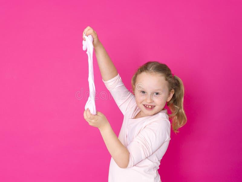 Девушка играет с желтым шламом перед розовой предпосылкой стоковые фото