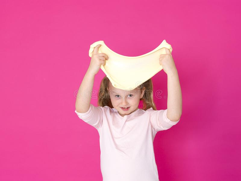 Девушка играет с желтым шламом перед розовой предпосылкой стоковое изображение rf