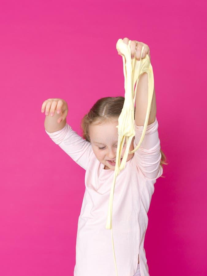 Девушка играет с желтым шламом перед розовой предпосылкой стоковые изображения