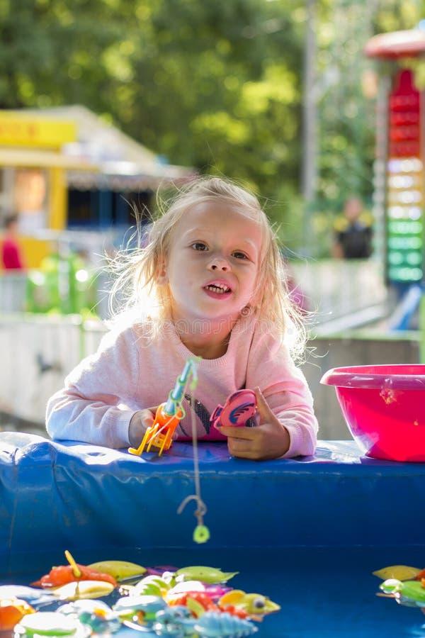 Девушка играя в парке гоня рыб игрушки стоковые фото