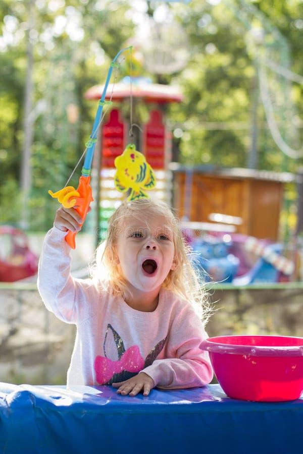 Девушка играя в парке гоня рыб игрушки стоковые фотографии rf