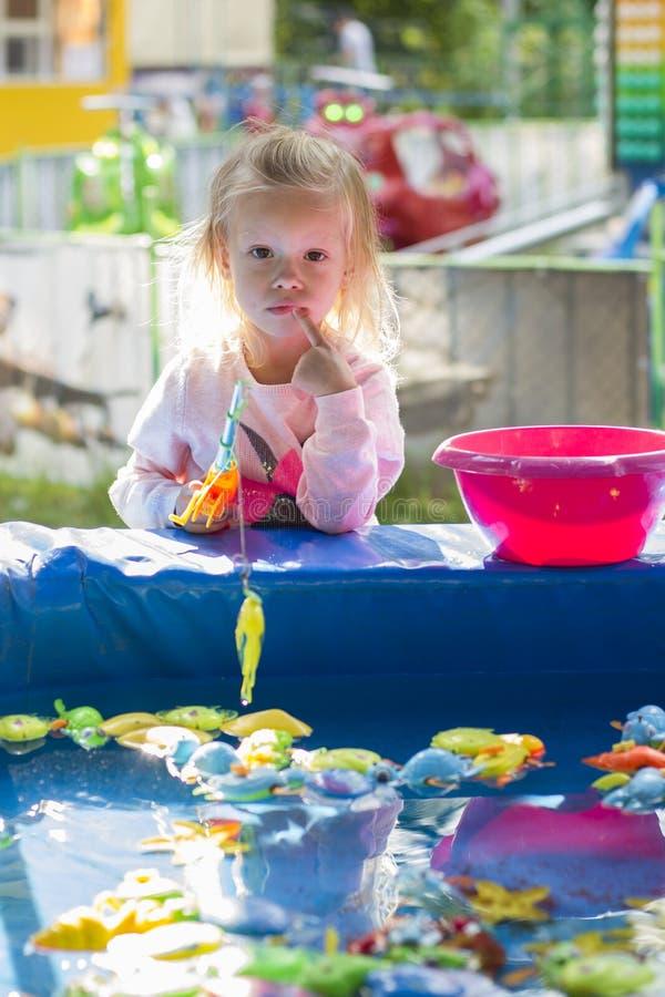 Девушка играя в парке гоня рыб игрушки стоковое изображение