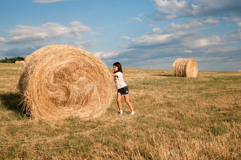 Девушка играя в поле со стогом сена стоковая фотография rf