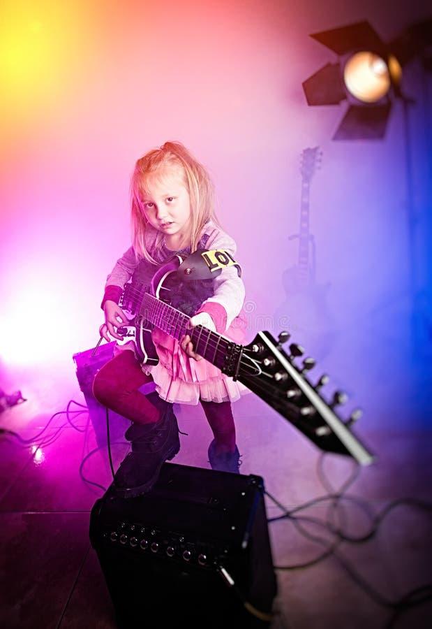 девушка играя гитару, гитариста ребенк стоковое фото rf
