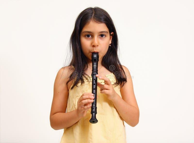 девушка играя детенышей рекордера стоковое фото