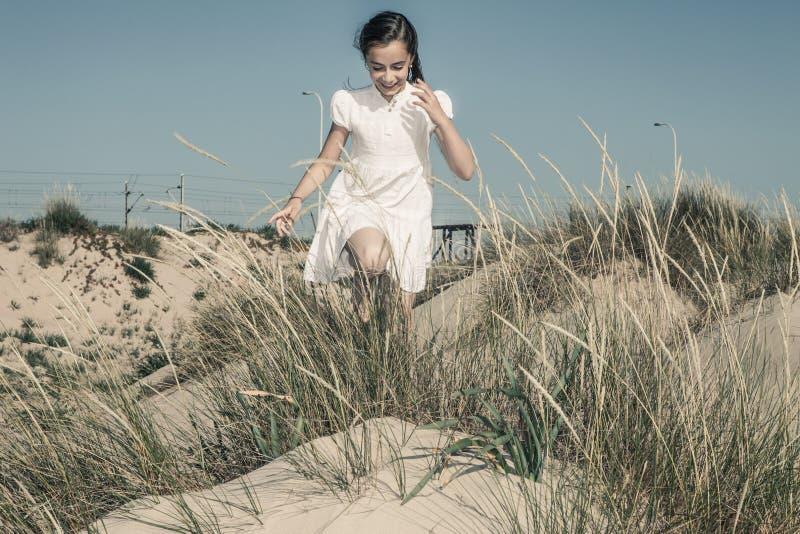 Девушка играя и смеясь над среди пшеницы стоковое изображение