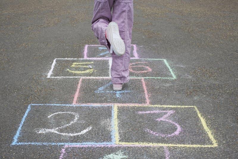 Девушка играя классики в спортивной площадке стоковая фотография