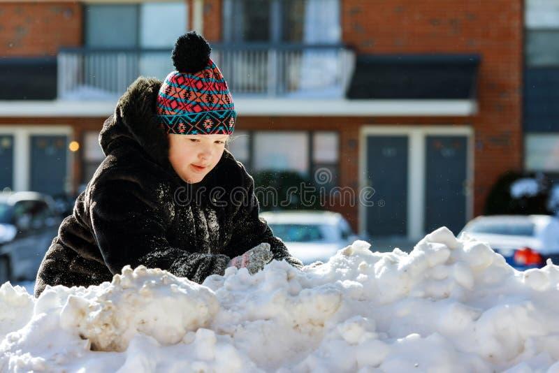Девушка играя со снегом около дома стоковые изображения