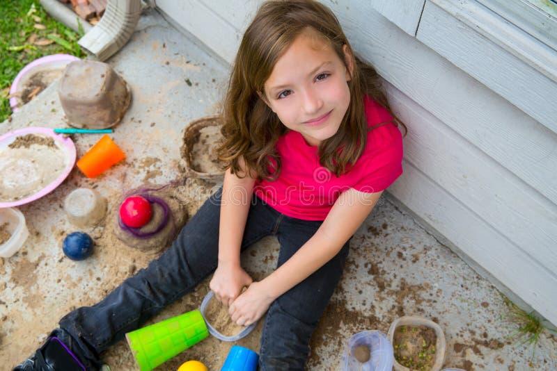 Девушка играя с грязью в портрете грязной почвы усмехаясь стоковое фото