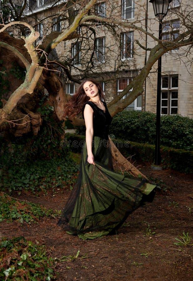 Девушка играя с ее викторианским платьем в парке стоковые изображения rf