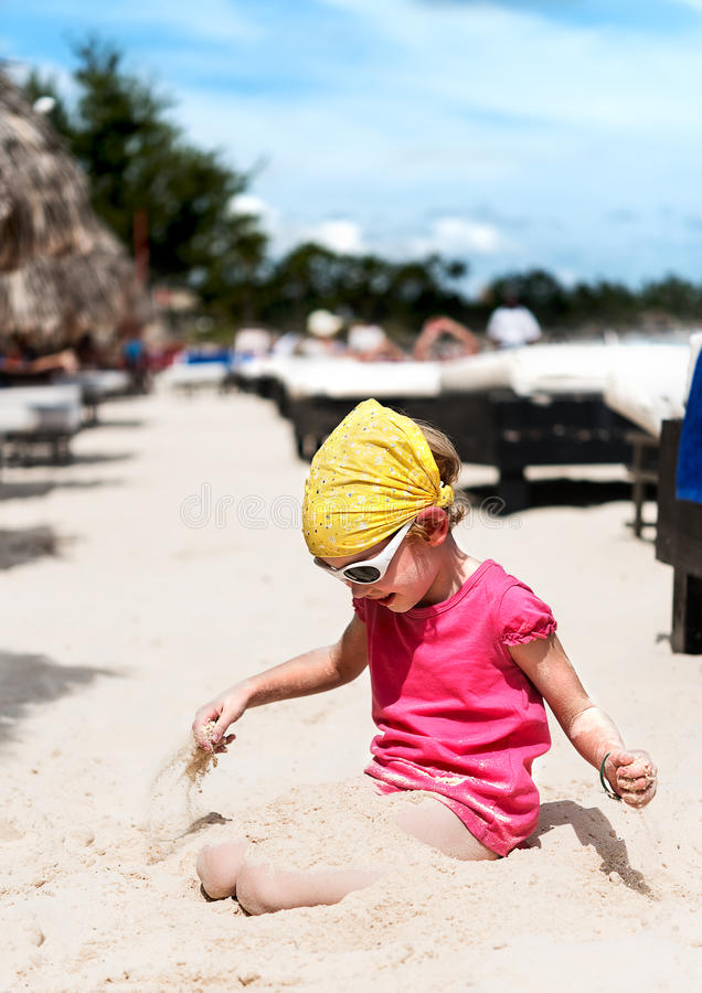 Девушка играя с песком на пляже стоковое изображение
