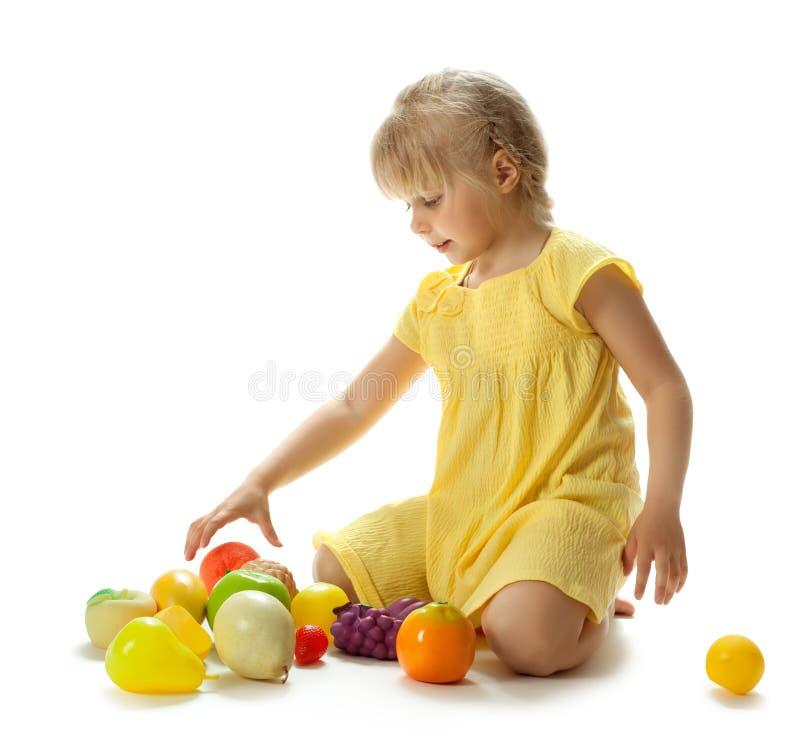Девушка играя с плодоовощами стоковые фотографии rf
