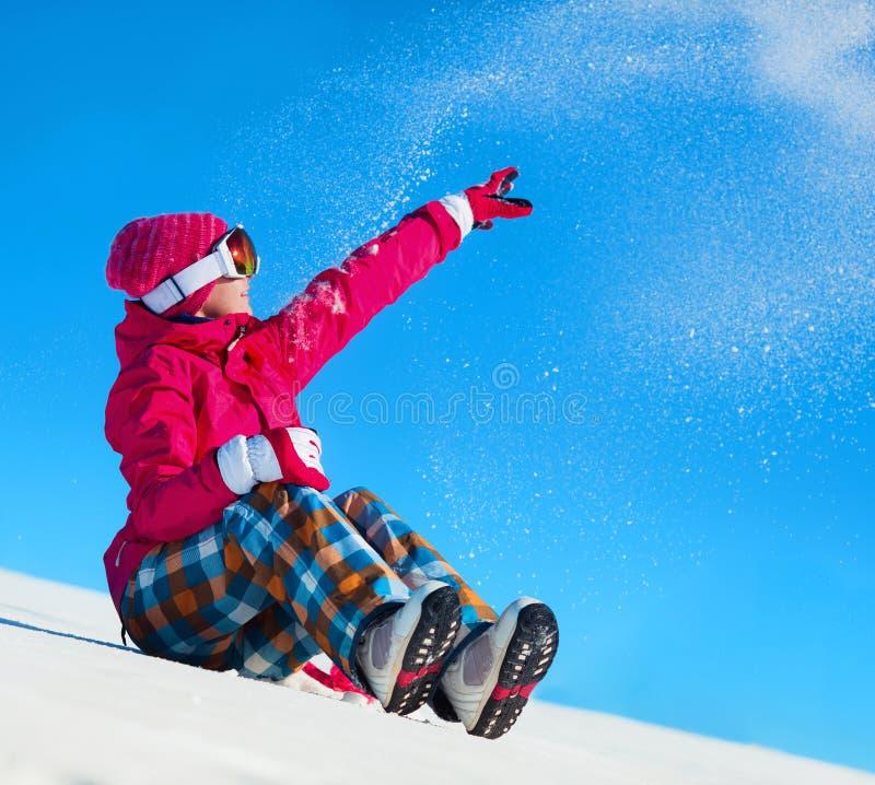 Девушка играя с снегом на курорте стоковые фото