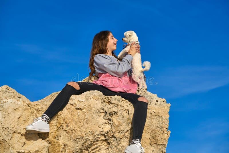 Девушка играя с собакой щенка maltichon на утесе стоковая фотография