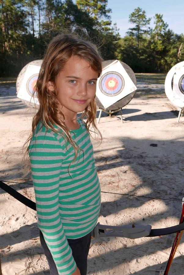 Девушка играя улыбки archery на камере стоковое изображение