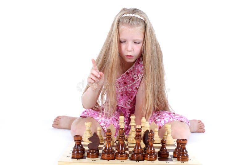 Девушка играя шахмат на белизне стоковое фото rf