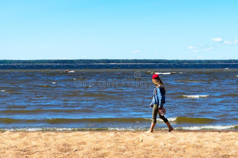Девушка идет босоногой морем стоковое фото