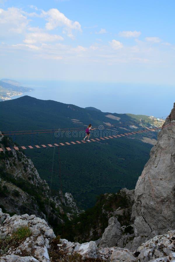 Девушка идет вдоль висячего моста над пропастью в горах Ai-Petri Крайность в горах стоковые изображения rf