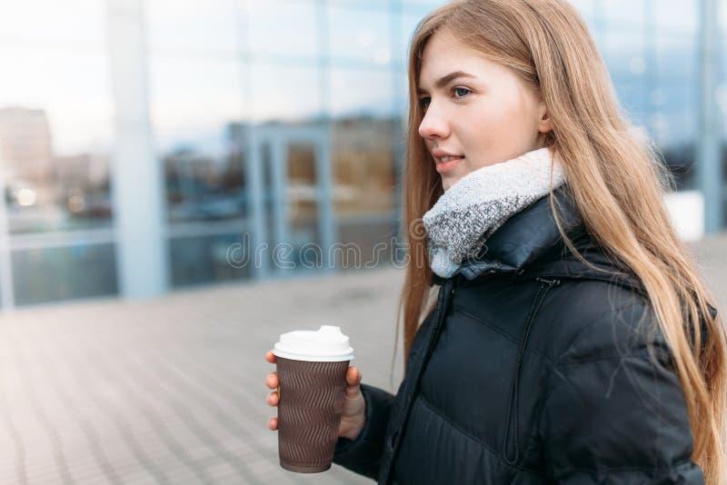 Девушка идет вниз с улицы с бумажным стаканчиком кофе, конца-вверх, хорошей погоды, женщины в изолированной куртке, стоковое фото rf
