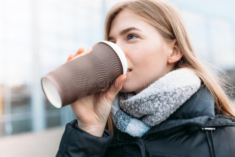 Девушка идет вниз с улицы с бумажным стаканчиком кофе, конца-вверх, хорошей погоды, женщины в изолированной куртке, стоковое изображение rf