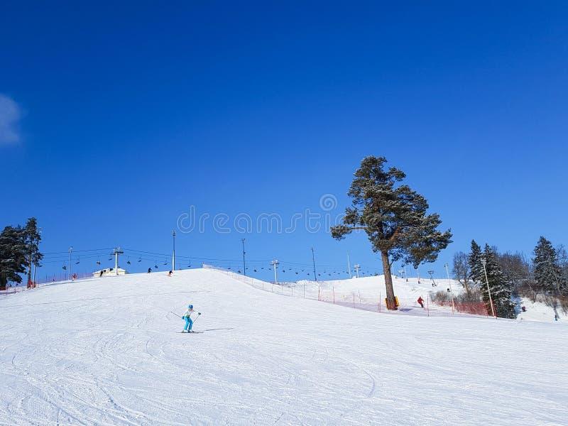 Девушка идет вниз с холма к лыжному курорту стоковое фото rf