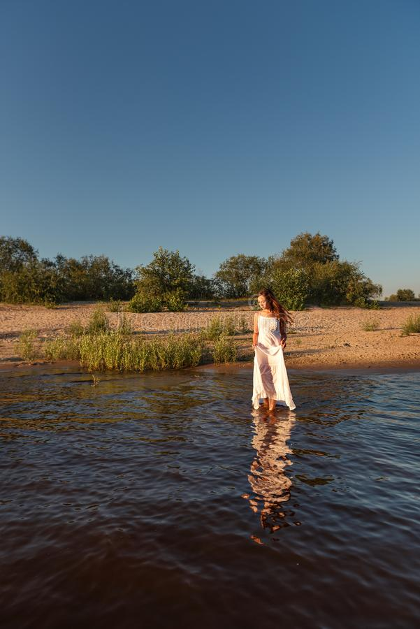 Девушка идет в воду на сумраке держа влажное белое платье лета стоковые изображения rf