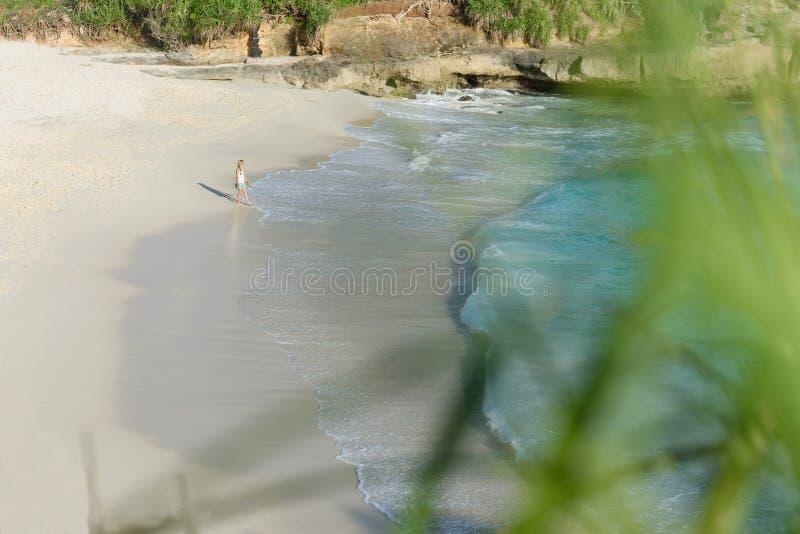 Девушка идя вдоль мечт пляжа на заходе солнца на Nusa lembongan, Бали, Индонезии 2 стоковые фотографии rf