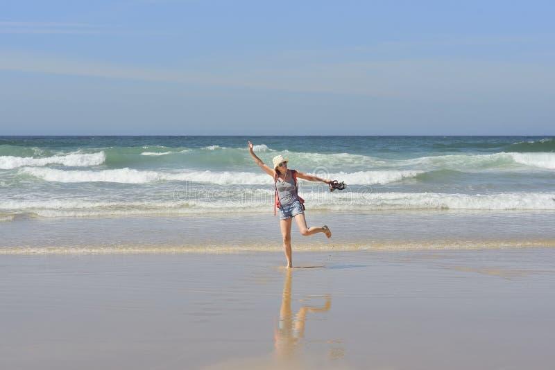 Девушка идя на пляж на заходе солнца стоковое фото rf