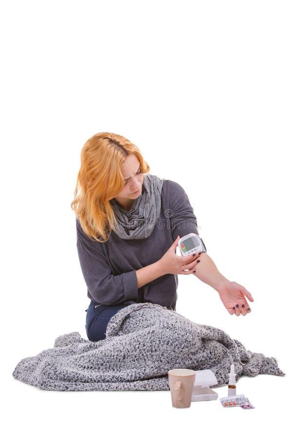 Девушка измеряет давление с электронным tonometer белизна изолированная предпосылкой стоковые изображения rf