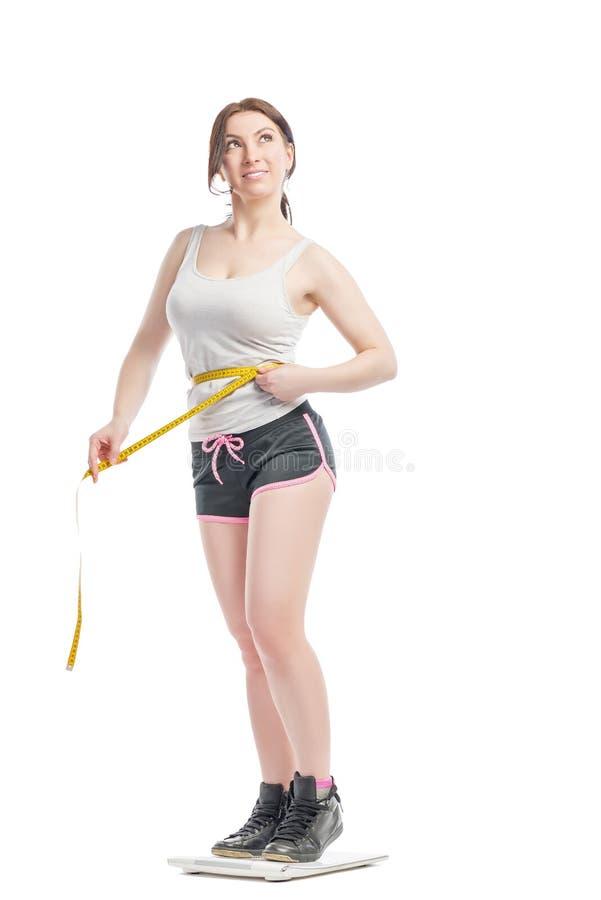 Девушка измеряет размер и вес стоковое изображение rf
