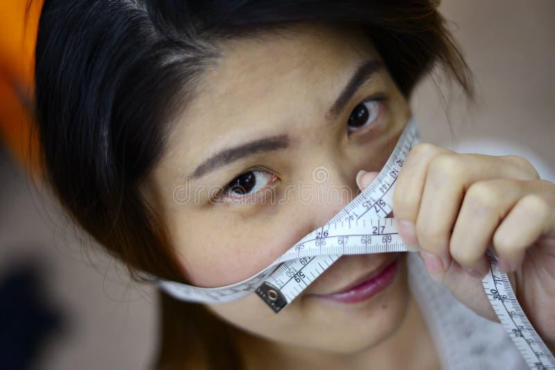 Девушка измеряя ее сторону стоковые фотографии rf
