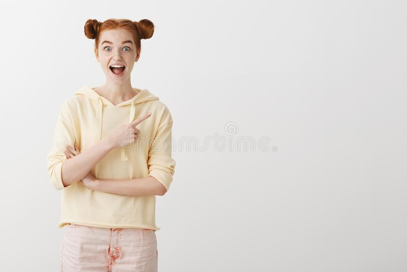 Девушка изумлена, не может ждать для того чтобы показать нам интересное место Студия сняла excited красивой молодой женщины с кра стоковые изображения rf