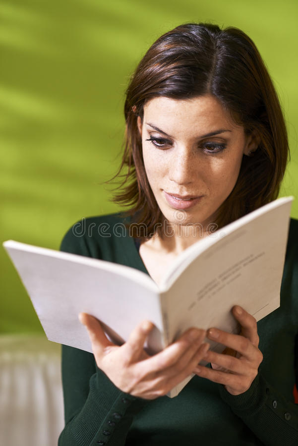 Девушка изучая литературу с книгой дома стоковое фото