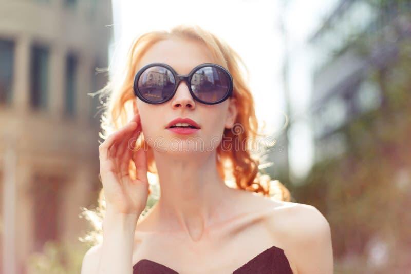 Девушка имбиря в солнечных очках на предпосылке зданий, подкрашиванном фото стоковые изображения