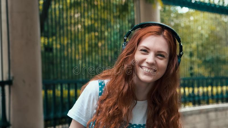 Девушка имбиря слушая музыку в больших наушниках стоковое изображение
