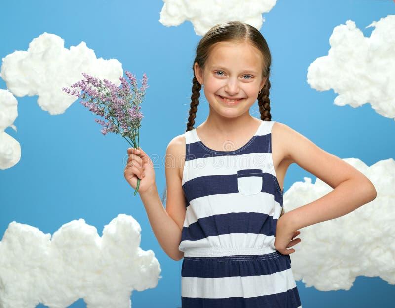 Девушка имеет букет цветков лаванды в ее руках, одетых в striped платье, представляя на голубой предпосылке с облаками хлопка, co стоковая фотография rf