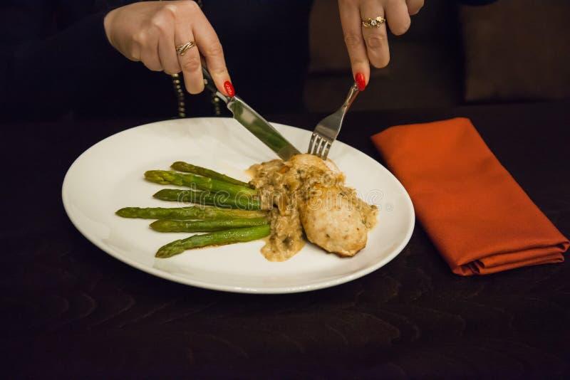 Девушка имеет блюдо Цыпленок и спаржа стоковое изображение
