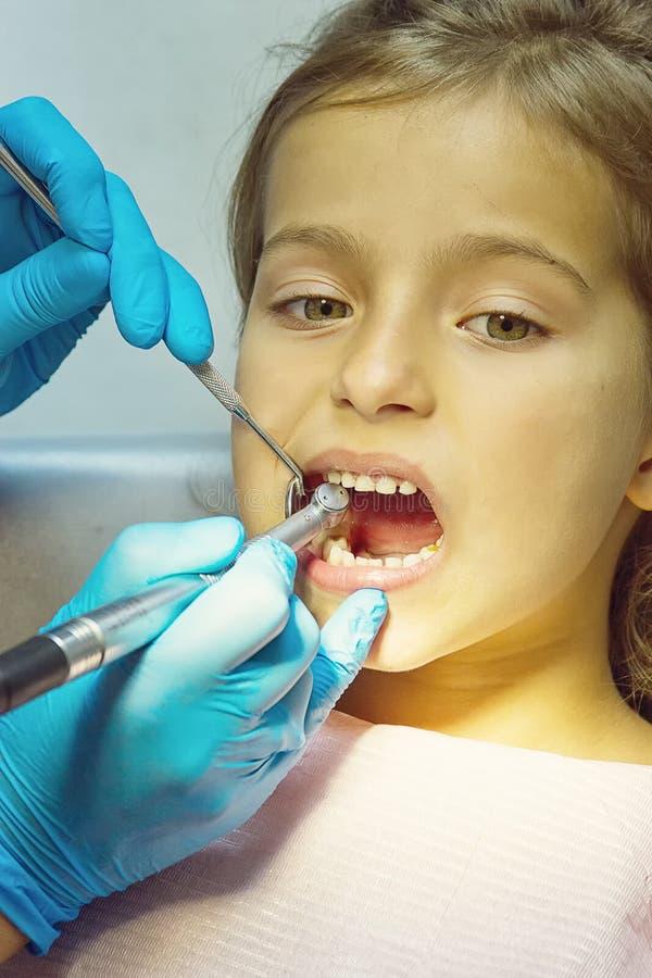 Девушка имеет ее зубы быть расмотренным дантистом стоковая фотография