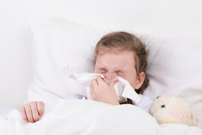 Девушка имеет лож жидкого носа в кровати стоковое фото rf