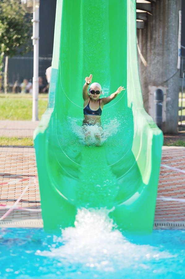 Девушка имеет потеху на скольжении воды стоковое фото