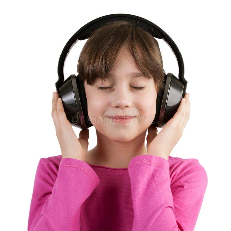 Девушка имея потеху слушая к музыке на наушниках стоковое фото