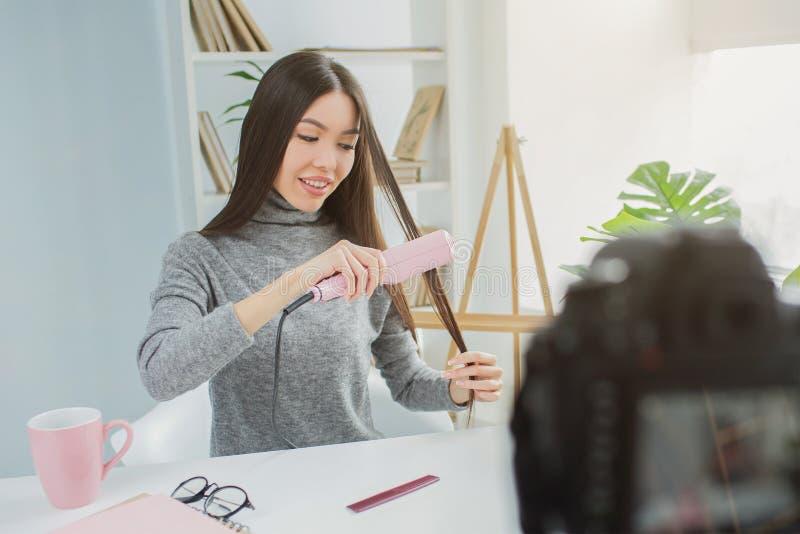 Девушка использует специальный прибор для straitning ее волосы Она записывает то на камере для ее блога красоты 15 детенышей женщ стоковое фото rf