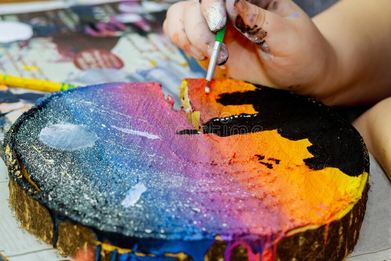 Девушка использует цветные краски, которые кистью кипятся в дереве стоковые фото