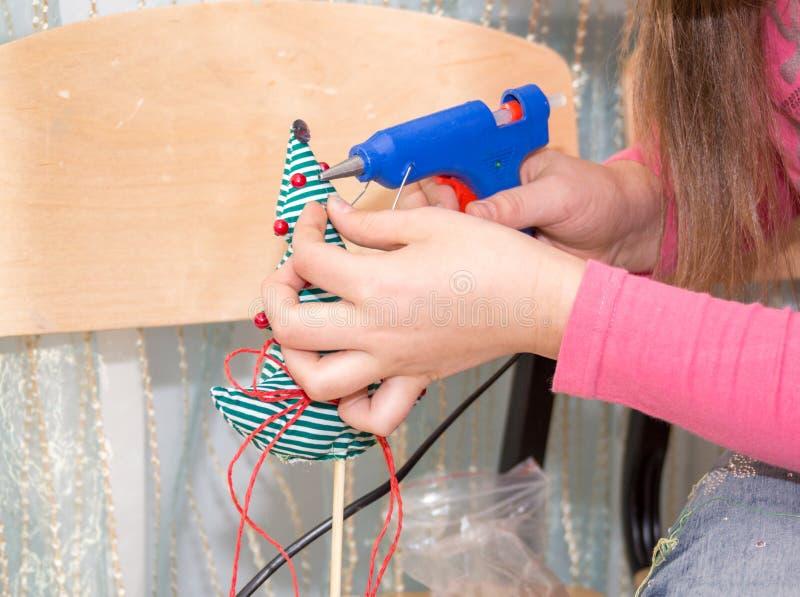 Девушка используя клей для того чтобы украсить рождественскую елку Handmade настоящий момент стоковые изображения