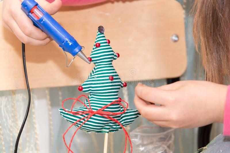 Девушка используя клей для того чтобы украсить рождественскую елку Handmade настоящий момент стоковое фото