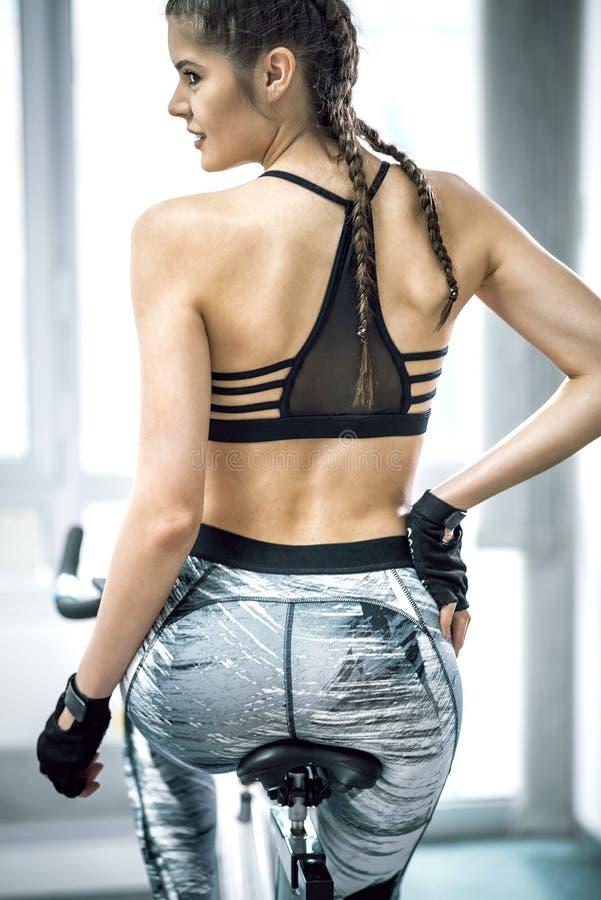 Девушка используя велосипед фитнеса стоковое изображение
